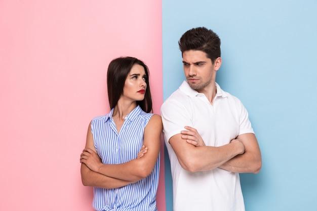 Foto di un uomo e una donna risentiti in abiti casual in piedi con le braccia conserte in lite, isolato su un muro colorato