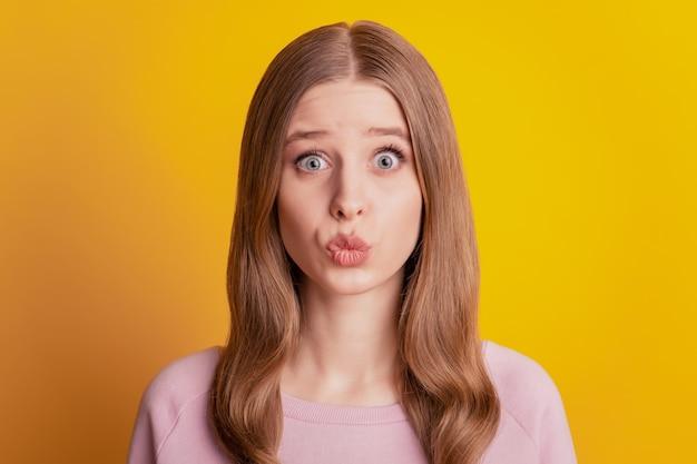 Foto di una ragazza romantica e affettuosa che invia un bacio d'aria alla telecamera su sfondo giallo