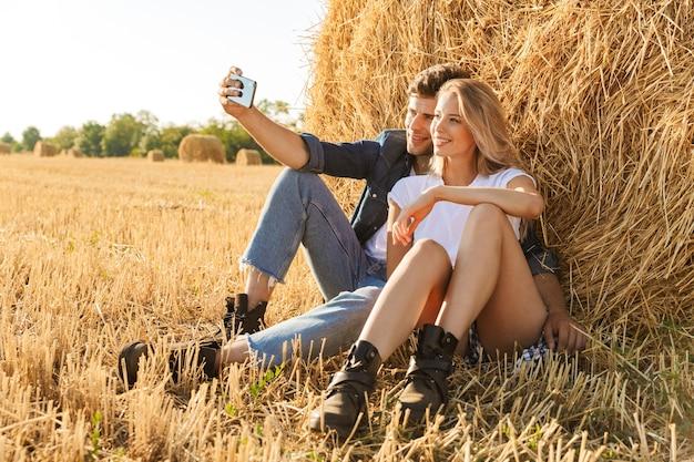 Foto di coppia romantica uomo e donna prendendo selfie seduti sotto un grande pagliaio in campo dorato, durante la giornata di sole