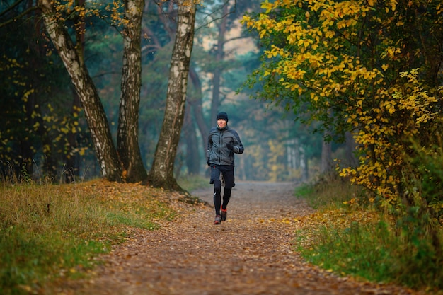 Foto di un atleta che corre nel parco autunnale