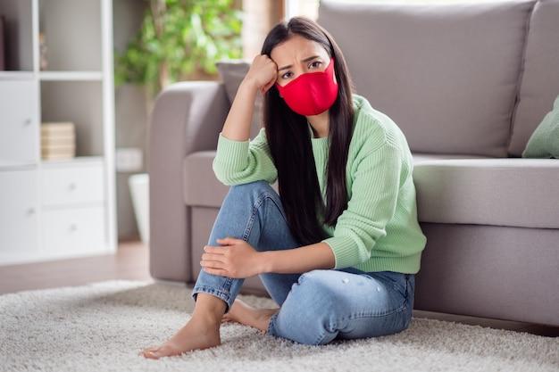 Foto di triste corona virus malato paziente signora asiatica sedersi pavimento tappeto divano tenere le ginocchia soffrire infezione malattia autoisolamento mantenere la distanza sociale non incontrare la famiglia stare a casa quarantena in casa