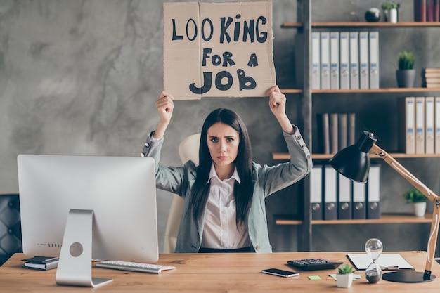 Foto di una ragazza triste e frustrata che ha perso il lavoro azienda virus corona quarantena crisi del mercato tenere testo in cartone cercare lavoro indossare giacca giacca sedersi tavolo scrivania nella postazione di lavoro