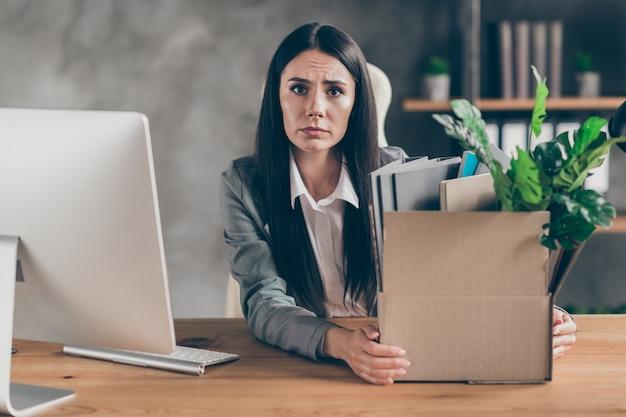 Foto di una ragazza triste e frustrata, agente di marketing, tenere in mano una scatola di carte con i suoi effetti personali, quarantena, crisi aziendale, lavoro perso, indossare giacca, sedersi, scrivania, scrivania, postazione di lavoro