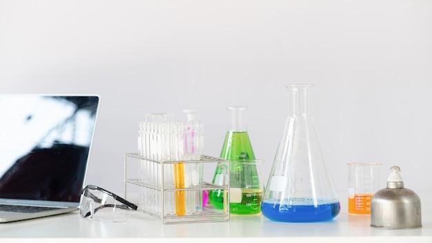 Foto dell'attrezzatura scientifica, della cristalleria di chimica e del computer portatile che uniscono sullo scrittorio funzionante bianco sopra la parete di bianco del laboratorio
