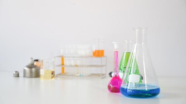 Foto dell'attrezzatura scientifica e della vetreria per chimica che uniscono sullo scrittorio funzionante bianco sopra la parete di bianco del laboratorio