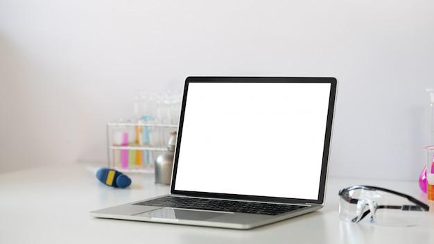 Foto dell'attrezzatura di esperimenti scientifici che mette sullo scrittorio funzionante bianco con il computer portatile bianco del computer dello schermo in bianco. computer portatile piatto, vetreria chimica, occhiali di sicurezza.