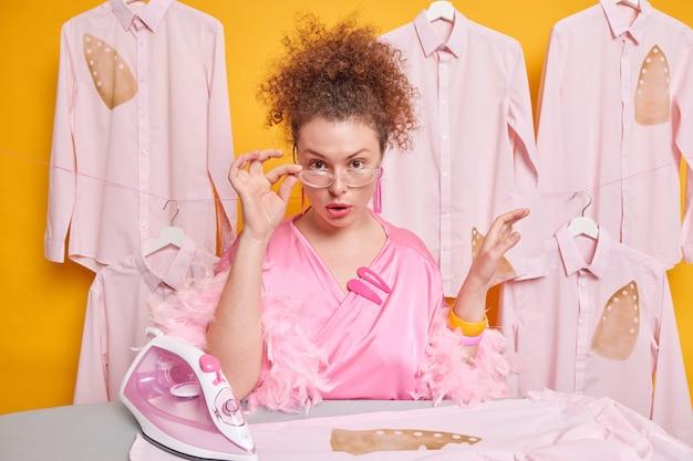 La foto della casalinga scrupolosa guarda attentamente da sotto gli occhiali trasparenti vestita con un abito domestico posa vicino all'asse da stiro, i vestiti dei ferri hanno una giornata impegnativa. concetto di lavoro domestico e responsabilità
