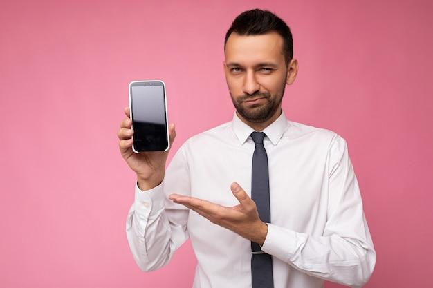 Foto di un bell'uomo sicuro di sé che indossa una camicia bianca casual e una cravatta isolata sul rosa
