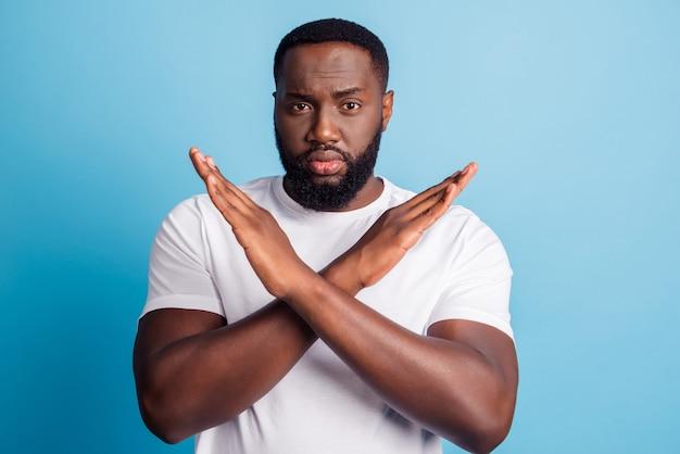 La foto di un uomo africano serio con le mani incrociate mostra un gesto di restrizione che indossa una maglietta bianca su sfondo blu