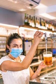 Sessione fotografica con una cameriera con una maschera in un bar. versando un bicchiere di birra pole e guardando sorridente