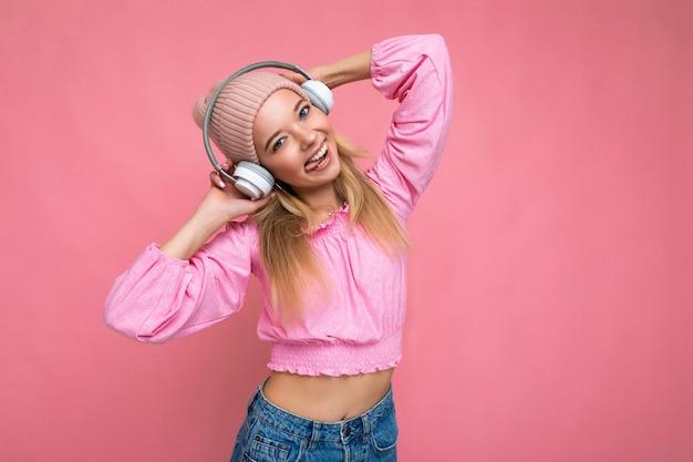 Foto di giovane donna bionda sorridente positiva attraente sexy che porta camicetta rosa e cappello rosa