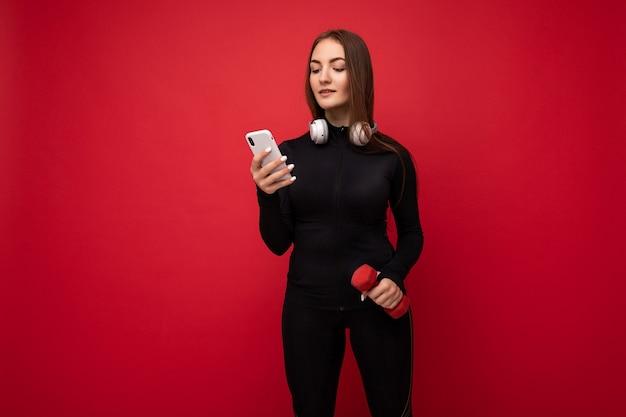 Foto di giovane donna castana positiva attraente sexy che indossa le cuffie bianche dei vestiti di sport neri