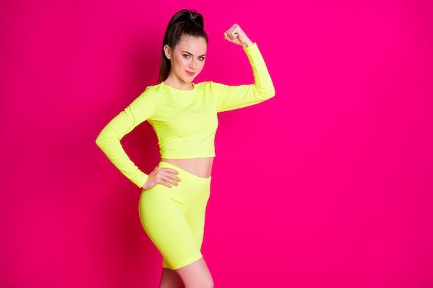 Foto di una donna brillante e forte che indossa un completo sportivo che mostra i muscoli che alzano il pugno della mano del braccio in vita isolato sfondo di colore rosa
