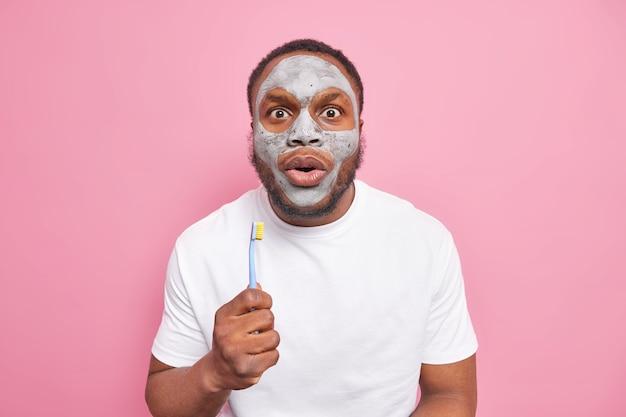Foto di un uomo barbuto scioccato tiene in mano uno spazzolino da denti