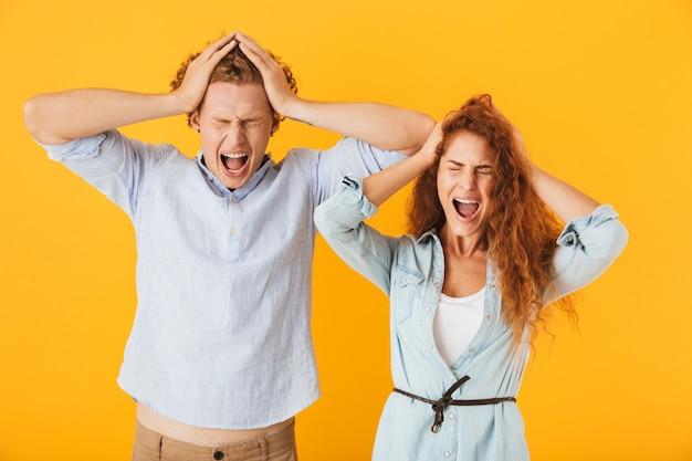 Foto di scioccato coppia confusa uomo e donna in abbigliamento di base urlando e afferrando le teste con gli occhi chiusi, isolate su sfondo giallo
