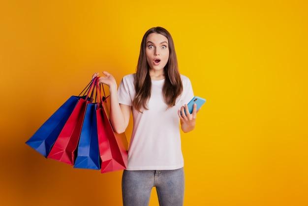 Foto di una donna scioccata che tiene affari legge un messaggio telefonico indossa una maglietta bianca in posa su sfondo giallo