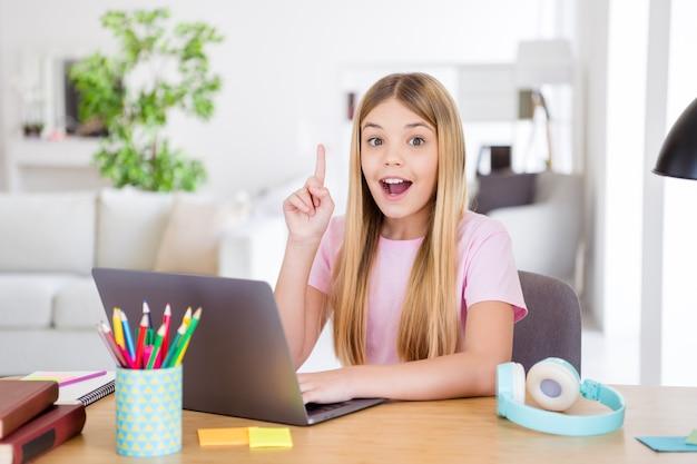 Foto di una bambina scioccata che si siede a un tavolo accogliente usa il laptop pensa che i pensieri risolvono il compito del lavoro a casa alza il dito indice in casa al chiuso