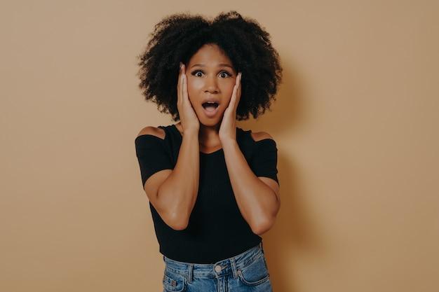 Foto di una signora dai capelli ricci dalla pelle piuttosto scura scioccata che si tiene per mano sugli zigomi non crede a causa dei prezzi bassi scontati, indossa una maglietta nera alla moda isolata su sfondo beige scuro