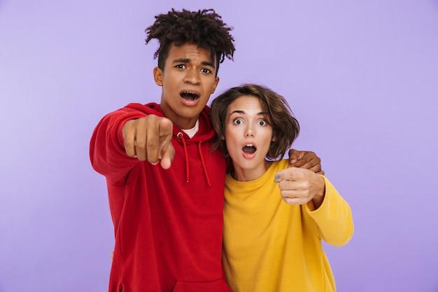 Foto di studenti scioccati di giovani amici di coppia in piedi isolati, che punta a te.