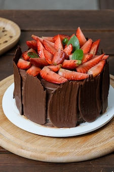 Servizio fotografico con torta al cioccolato da decorare. torta al cioccolato ricoperta di fragole, foglie di basilico fresco, marmellata di more e piatti di cioccolato intorno.