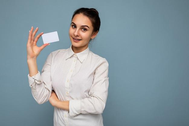 Scatto fotografico di una giovane donna bruna sorridente positiva attraente che indossa una camicetta bianca