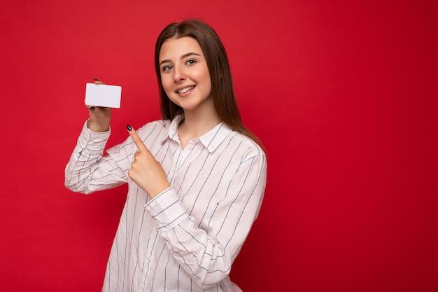Scatto fotografico di una giovane donna bionda scura sorridente positiva attraente che indossa una camicetta bianca