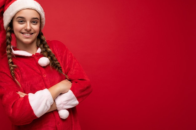 Scatto fotografico di una bella ragazza bruna sorridente positiva felice con le trecce che indossa abiti con clausola di babbo natale