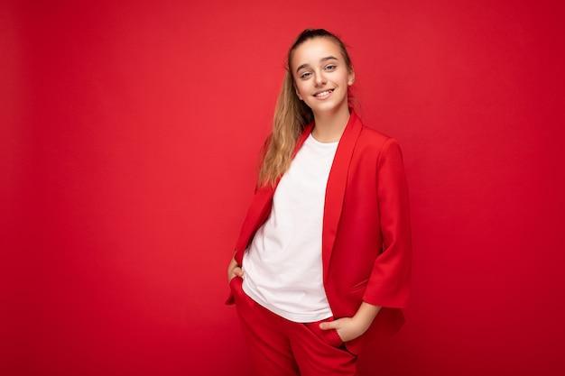 Foto scattata di bella bambina bruna sorridente felice che indossa giacca rossa alla moda e maglietta bianca