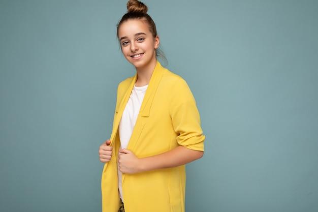 Foto scattata di bella bambina bruna sorridente felice che indossa giacca gialla alla moda e maglietta bianca