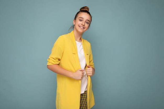 Foto scattata di bella bambina bruna sorridente felice che indossa giacca gialla alla moda
