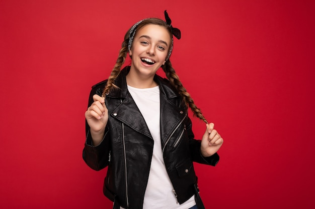 Foto scattata di bella bambina bruna sorridente felice con le trecce che indossa giacca di pelle nera alla moda e t-shirt bianca