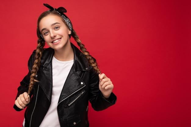 Foto scattata di bella bambina bruna sorridente felice con le trecce vestita di nero alla moda