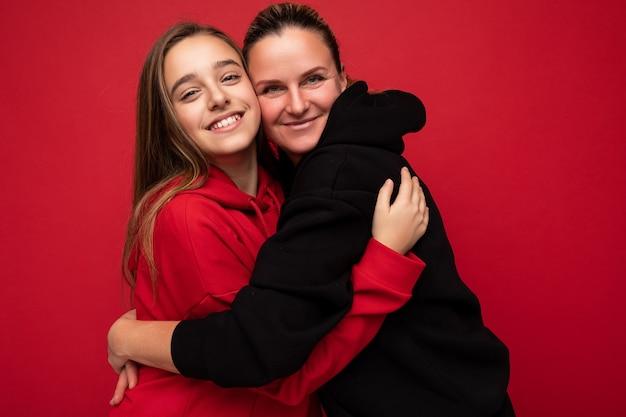 Scatto fotografico di una bellissima figlia bruna sorridente positiva che indossa un'elegante felpa con cappuccio rossa e un adulto