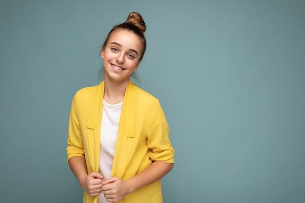 Foto scattata di bella bambina bruna sorridente positiva che indossa giacca gialla alla moda e maglietta bianca