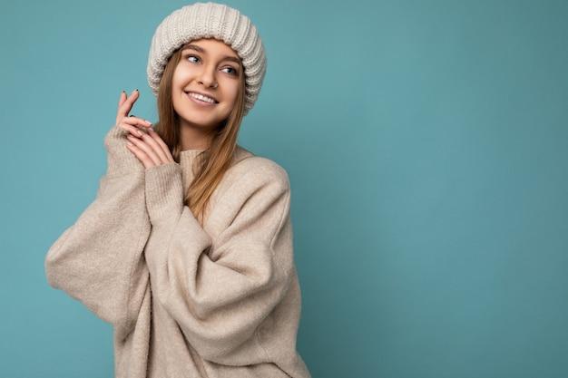Foto scattata di bella giovane donna bionda scura sexy sorridente positiva isolata su sfondo blu