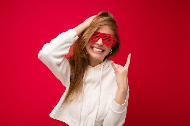 Foto scattata di bella giovane donna bionda positiva che indossa abiti casual e occhiali ottici alla moda