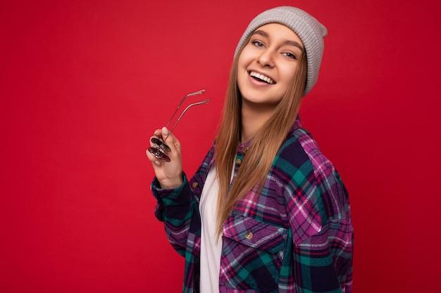 Foto scattata di bella giovane donna bruna positiva che indossa abiti casual estivi e tiene occhiali da sole eleganti isolati su una parete di sfondo colorato che guarda l'obbiettivo. copia spazio