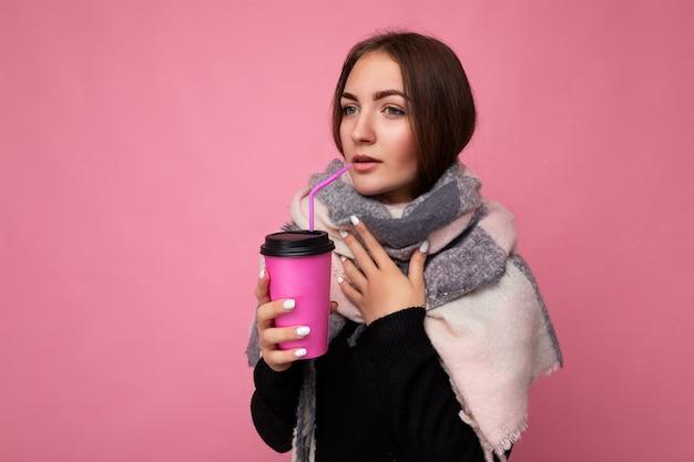 Foto scattata di bella giovane donna bruna sconvolta che indossa un maglione nero e sciarpa calda isolata