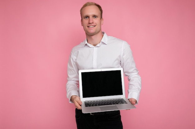 Foto colpo dell'uomo biondo bello che tiene il computer portatile del computer con lo schermo vuoto del monitor con lo spazio della copia e di derisione che porta la camicia bianca che guarda l'obbiettivo che indica al netbook isolato sopra fondo rosa.