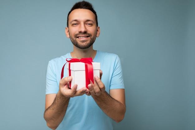 Scatto fotografico di un bel giovane bruna con la barba lunga sorridente positivo isolato su una parete di sfondo blu che indossa una t-shirt blu che tiene in mano una scatola regalo bianca con un nastro rosso e che guarda l'obbiettivo