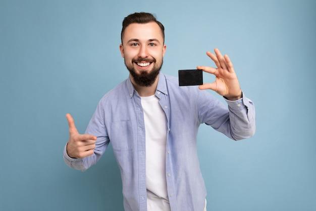 Scatto fotografico di bel giovane barbuto bruna sorridente che indossa elegante camicia blu e t-shirt bianca isolato su sfondo blu muro in possesso di carta di credito guardando la fotocamera.
