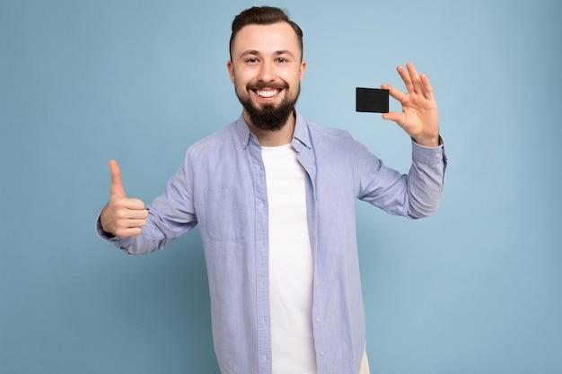 Foto colpo di bello sorridente bruna barbuto giovane uomo che indossa elegante camicia blu e t bianca