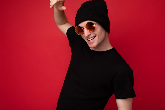 Scatto fotografico di un bel giovane sorridente che indossa una t-shirt nera per mockup cappello nero e occhiali da sole eleganti isolati su un muro di fondo rosso che guarda l'obbiettivo e si diverte.