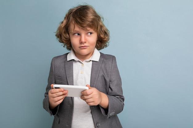 Foto colpo di bel ragazzo bambino sospetto con i capelli ricci che indossa abito grigio tenendo e utilizzando il telefono