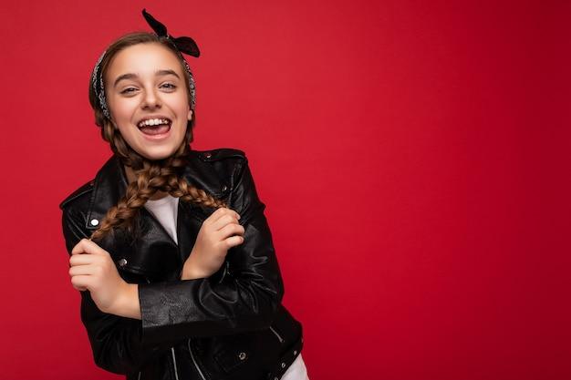 Scatto fotografico di una piccola adolescente femmina bruna sorridente piuttosto positiva con le trecce