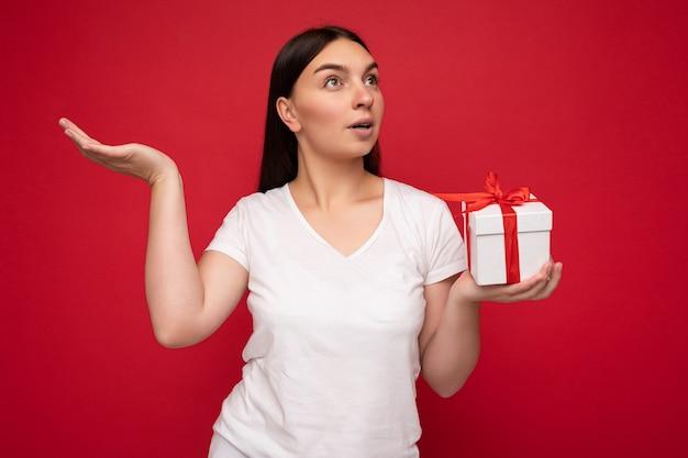 Scatto fotografico di una giovane donna brunet sorpresa piuttosto positiva isolata su una parete di sfondo colorata che indossa un look alla moda che tiene in mano una confezione regalo e guarda di lato.