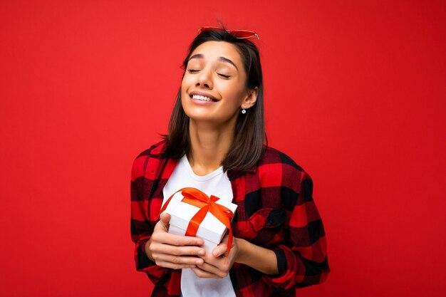 Scatto fotografico di una giovane donna bruna piuttosto positiva isolata su un muro di sfondo rosso che indossa una t-shirt casual bianca e una camicia rossa e nera che tiene in mano una confezione regalo bianca con un nastro rosso e si gode