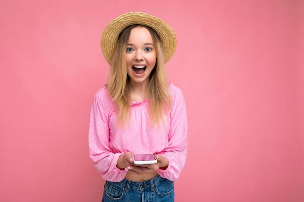 La foto ha sparato della giovane donna di bell'aspetto positiva attraente stupita sorpresa che porta alla moda casuale