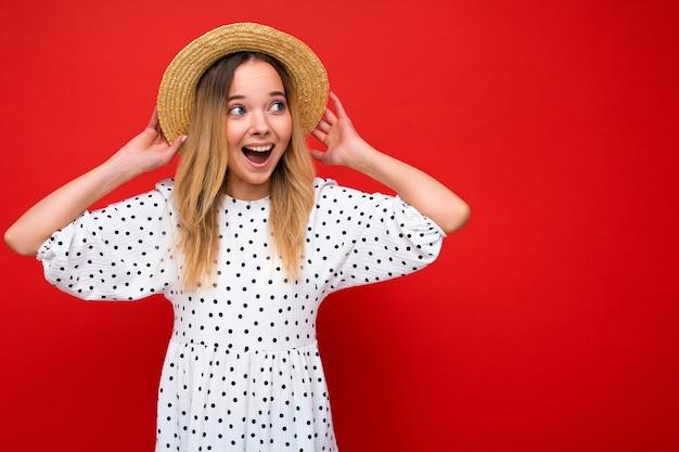 Scatto fotografico di una giovane bella donna bionda felice e carina che indossa un abito casual e un cappello di paglia