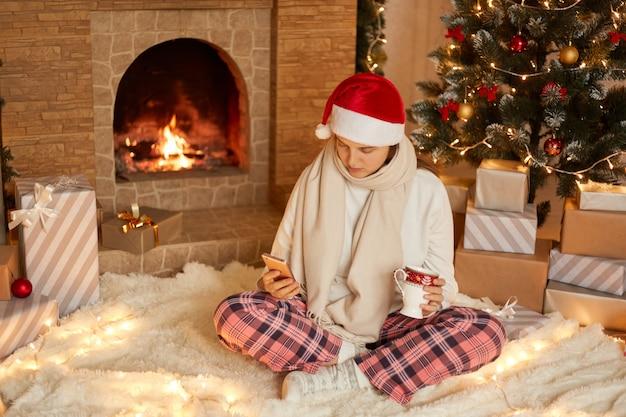 La foto della signora malata si siede nel soggiorno festivo utilizzando il cellulare e tiene la tazza della bevanda